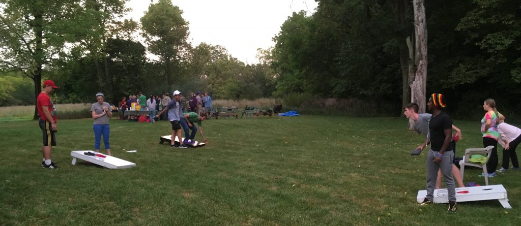 Students play corn hole at the university's nature preserve as part of the annual party hosted by the Matthewses to help build community.