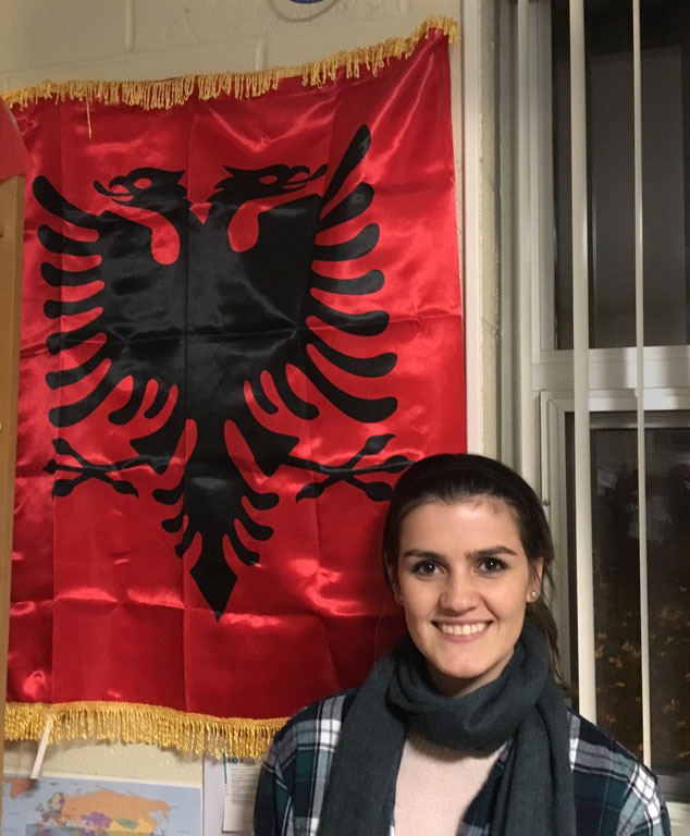 Junior Irena Xhari stands with the Albanian flag. Photo by Erika Byler
